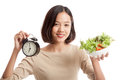 Young Asian business woman with clock and salad Royalty Free Stock Photo