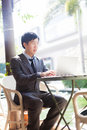 Young Asian businessman working with his laptop in outdoor scene