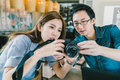Young Asian couple learning to use mirrorless digital camera together at coffee shop Royalty Free Stock Photo