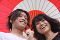 Young Asian couple smiling with umbrella Royalty Free Stock Images