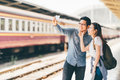 Young Asian couple traveler taking selfie together using smartphone waiting for trip at train station platform in Asia Royalty Free Stock Photo