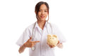Young Asian female doctor point to a pig bank coin Royalty Free Stock Photo
