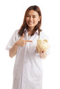 Young Asian female doctor point to a pig bank coin. Royalty Free Stock Photo