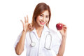 Young Asian female doctor show OK with apple Royalty Free Stock Photo