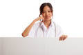 Young Asian female doctor standing behind blank white billboard Royalty Free Stock Photo