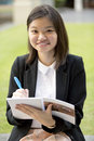 Young asian female executive writing on notepad smiling Royalty Free Stock Photos