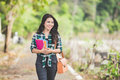 Young asian female student holding books while walking on the pa Royalty Free Stock Photo
