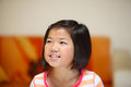 Young asian girl looks off camera with happy smile shallow depth of field Stock Photos
