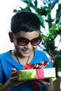 Young asian kid on sunglass look at his christmas present white background Royalty Free Stock Photo