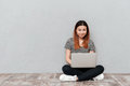 Young asian looking camera and smiling while using laptop Royalty Free Stock Photo
