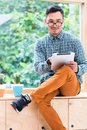 Young Asian man browsing the internet on a tablet PC in the office Royalty Free Stock Photo