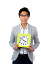Young asian man holding a clock over white background Royalty Free Stock Photo