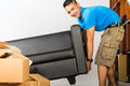 Young asian man lifting a couch real estate market indonesian sofa put it away Royalty Free Stock Image