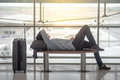 Young Asian man lying on bench in airport terminal Royalty Free Stock Photo