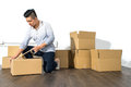 Young asian man moving house Packing cardboard using adhesive Royalty Free Stock Photo