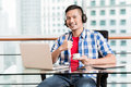Young asian man in office having coffee giving thumbs up sign Royalty Free Stock Photo