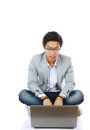 Young asian man sitting on the floor and using laptop over white background Stock Images