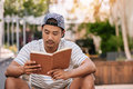 Young Asian man sitting on stairs outside reading a book Royalty Free Stock Photo
