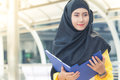 Young asian muslim business woman smiling and holding file document and standing at capital city. Royalty Free Stock Photo