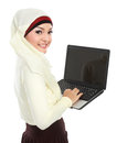 Young asian muslim woman in head scarf using laptop computer isolated over white background Stock Image