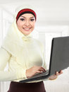 Young asian muslim woman in head scarf using laptop computer isolated over white background Stock Photos