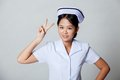 Young asian nurse show victory sign on gray background Royalty Free Stock Photography