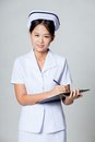Young asian nurse writing on a clipboard and smile gray background Royalty Free Stock Photos