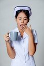 Young asian nurse yawn with a cup of coffee on gray background Royalty Free Stock Photos