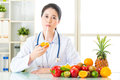 Young asian nutritionist drinking orange juice Royalty Free Stock Photo