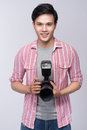 Young asian photographer holding digital camera, while working i