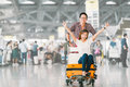 Asian tourist couple happy and excited together for the trip, girlfriend sitting and cheering on baggage trolley or luggage cart Royalty Free Stock Photo