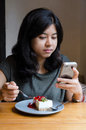 Young asian woman chating mobile phone with a cake in cafe Royalty Free Stock Photos
