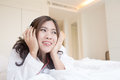 Young asian woman enjoying the music at bed in home Stock Photos