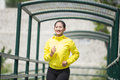 Young asian woman exercising outdoor in yellow neon jacket, jogging Royalty Free Stock Photo