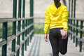 Young asian woman exercising outdoor in yellow neon jacket, stretching Royalty Free Stock Photo