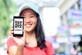Young asian woman hold smart phone show quick response coupon code on shopping street Royalty Free Stock Photo