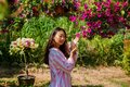 Young asian woman is holding flowers in the garden in the spring.