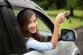 Young asian woman inside a car hold the key out from the window portrait of Royalty Free Stock Photo