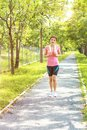 Young asian woman jogging during Outdoor Workout in a Park. Royalty Free Stock Photo