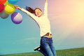 Young asian woman jumping with colored balloons Royalty Free Stock Photo