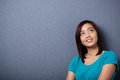 Young asian woman lost in thought standing against a dark background with copyspace looking up into the air with a smile Stock Photos