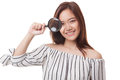 Young Asian woman with a magnifying glass. Royalty Free Stock Photo