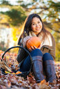 Young asian woman at the park holding a pumpkin in autumn sitting in a pile of leaves Royalty Free Stock Photos