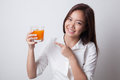 Young Asian woman point to orange juice.