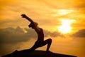Young asian woman practicing yoga warrior pose at sunset Stock Photo