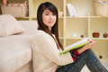 Young asian woman reading book at home Royalty Free Stock Photography