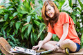 Young asian woman reading fashion magazine chinese girl sitting on a bench in a tropical environment and a she is conscious Royalty Free Stock Photos