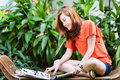 Young asian woman reading fashion magazine chinese girl sitting on a bench in a tropical environment and a she is conscious Stock Photography