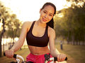 Young asian woman riding bike outdoors at sunset and beautiful bicycle in park smiling and cheerful fitness sport and exercise Stock Photo