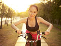 Young asian woman riding bike outdoors at sunset and beautiful bicycle in park smiling and cheerful fitness sport and exercise Royalty Free Stock Photo
